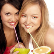 Blonde and the brunette drink juice — Stock Photo