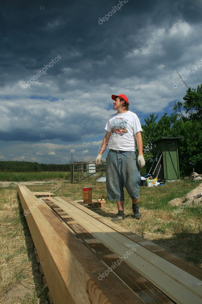 Painter painting the wooden logs — Stock Photo #1849358