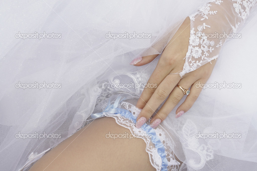 Bride putting garter on leg.  Stock Photo #1845796