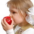 The girl biting an apple on a white — Stock Photo