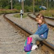 Little girl with a backpack on railway — Stock Photo