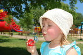 The girl blows a soap bubble — Stock Photo