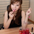 Chinese lady applying lipstick — Stock Photo