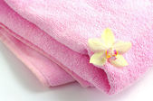 Flower of orchid on spa towel — Stock Photo