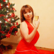 Beautiful woman under Christmas tree with glass of champagne — Stock Photo