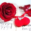 Royalty-Free Stock Photo: Red rose and petals on music sheet with fabric heart