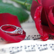 Red rose and its petals, ring on music sheet — Stock Photo #1852603