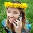 Stock Photo: Blonde happy girl with dandelion diadem talking on mobile