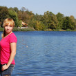 Girl on blue water lake in the forest — Stock Photo #1856239