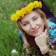 Girl with dandelion diadem over green grass — Stock Photo #1856343