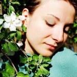 Beautiful woman among blooming cherry tree — Stock Photo