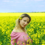 Beautiful girl among blooming rapeseed oilseed field — Stock Photo