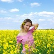 Beautiful girl among blooming rapeseed oilseed field — Stock Photo
