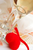 Two glasses of champagne with red fabric heart — Stock Photo