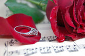 Red rose and its petals, ring on music sheet — Foto Stock
