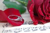 赤いバラとその花びら、音楽シートのリング — ストック写真