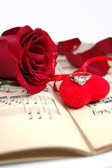 Red rose and petals on music sheet with fabric heart — Stock Photo