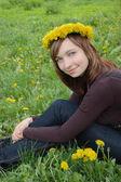 Beautiful girl with dandelion diadem — Stock Photo