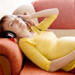 图库照片: Pregnant womwith headphones