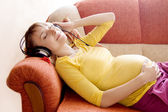 Pregnant woman with headphones — Stockfoto