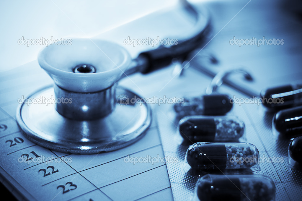 Stethoscope and pills over notebook blue toned  Stock Photo #1893898