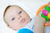 Little baby boy holding rattle — Stock Photo