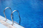 Fragment of swimming pool with ladder — Stock Photo
