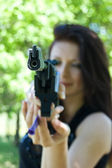 Woman aiming pneumatic gun — Stockfoto