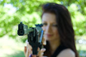 Woman firing with pneumatic gun — Stockfoto