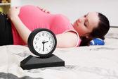 беременная женщина лежа и будильник — Стоковое фото