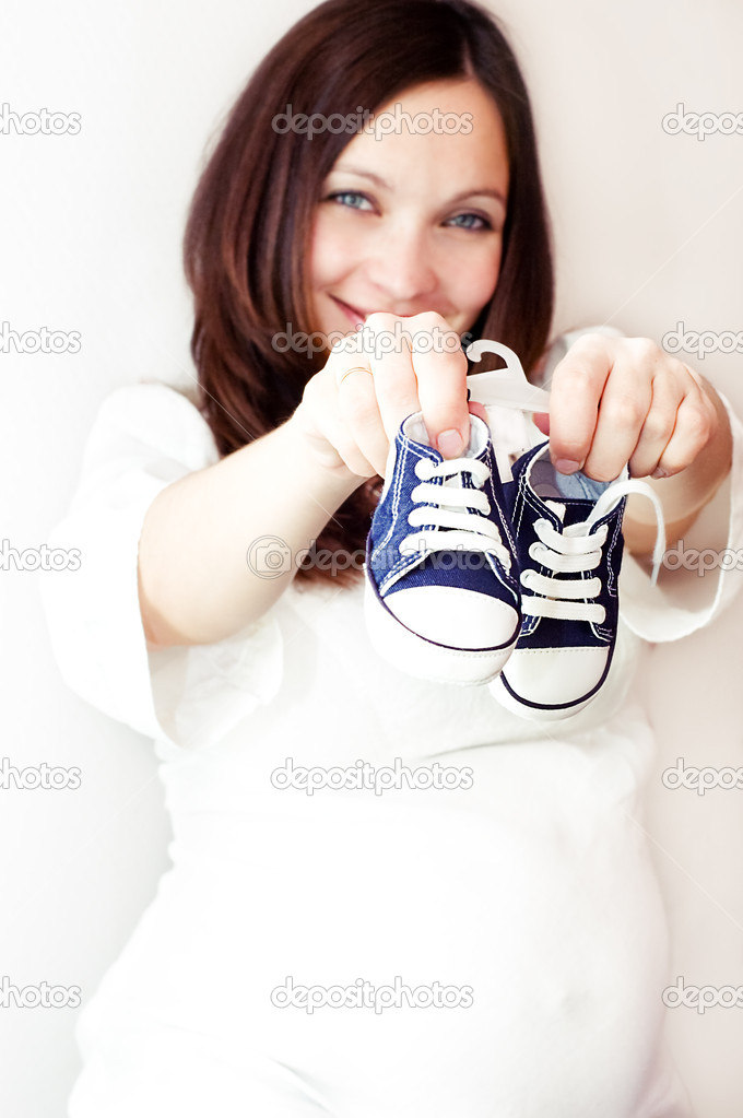 Pregnant woman holding blue tiny shoes in hands, focus on shoes — Stock Photo #1966503