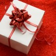White gift box with red satin ribbon - Stock Photo