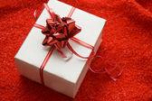 Białe pudełko z czerwona wstążka satynowa — Zdjęcie stockowe
