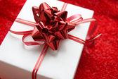 Geschenkdoos met rode satijnen lint — Stockfoto