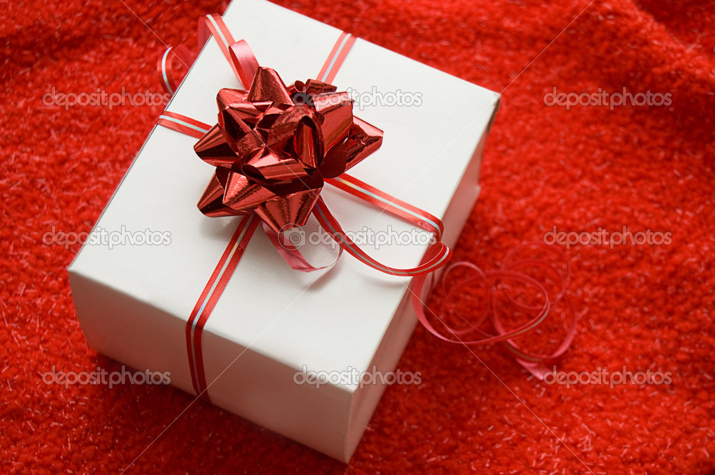 White gift box with red satin ribbon on red background — Stock Photo #2068266