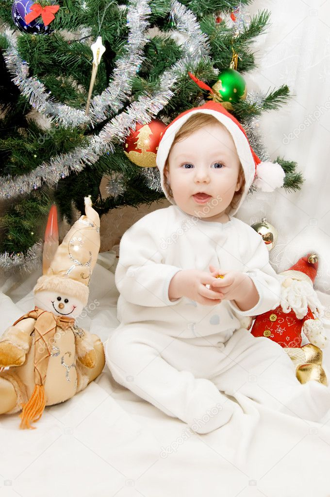 Baby in santa hat sitting under Christmas tree — Stock Photo #2069001