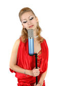 Girl in a red dress with a microphone — Stock Photo