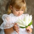 Girl in a white dress with a lily — Stock Photo