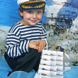 Royalty-Free Stock Photo: The boy in the sea with the navy dress