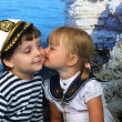 Girl kissing a boy in the Marine dress - Stock Photo