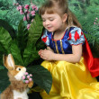 Girl dressed as Snow White and the hare - Stock Photo