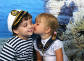 Girl kissing a boy in the Marine dress — Stock Photo