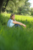 Young girl sitting in the tall grass — Stock Photo