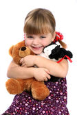 Girl embracing favorite toys — Stock Photo