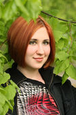 Beautiful girl in the green branches — Стоковое фото