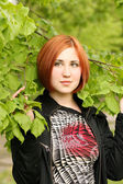 Beautiful girl in the green branches — Stock Photo