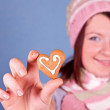 Girl holding one heart cookie — Stock Photo