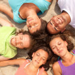 Teenagers lying on  beach in a circle — Stock Photo