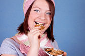 Smiling girl eating a cookie — Stock Photo