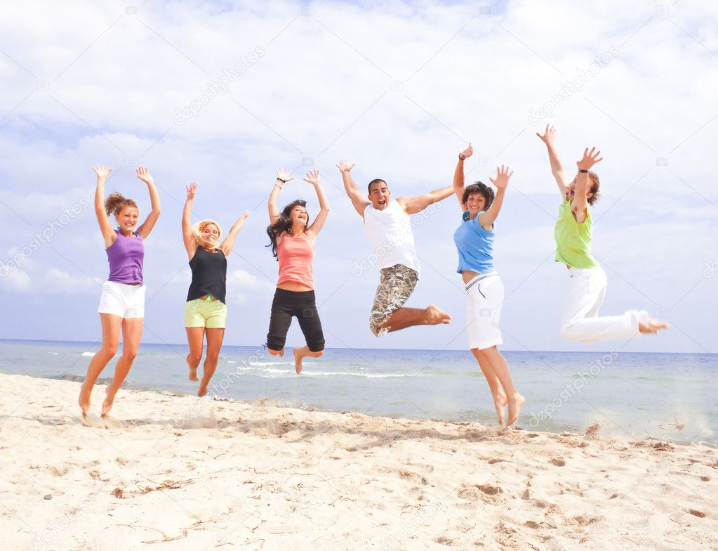 Happy jumping on the beach by the sea — Stock Photo #1856384